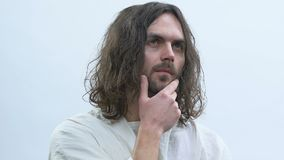 Jesus que toca no queixo contra o fundo branco, pensando sobre pecadores de salvamento video estoque