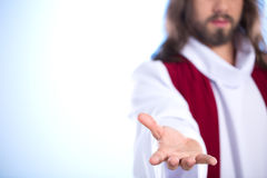 Jesus reaching out his hand. Silhouette of Jesus reaching out hand, isolated on bright background Stock Photo