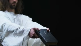 Jesus in robe die heilige bijbel tonen aan camera, geloof en overtuiging, donkere achtergrond stock video