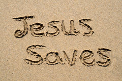 Jesus saves. Jesus saves, written on a sandy beach