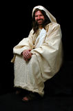 Jesus Sitting. And smiling over a black background Stock Photos