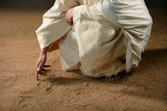 Jesus som skriver i sanden arkivfoto