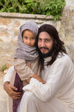 Jesus talking to a little girl. Biblical scene when Jesus says, let the little children come to me, blessing a little girl. Historical reenactment at an old Stock Photography