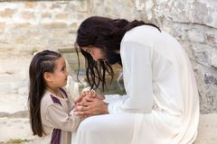 Jesus teaching a little girl. Biblical scene when Jesus says, let the little children come to me, blessing a little girl. Historical reenactment at an old water Royalty Free Stock Images