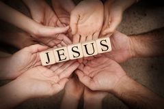 Jesus. Team Holding Building Blocks spelling out Jesus royalty free stock image