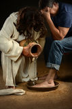 Jesus Washing Feet of Man. Jesus washing feet of men wearing jeans stock images