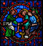 Jesus washing feet of Saint Peter on Maundy Thursday - Stained G. Stained glass window depicting Jesus washing the feet of Saint Peter at the Last Supper on Stock Images