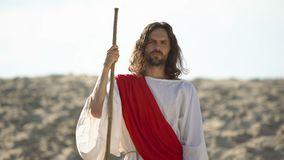 Jesus with wooden staff standing in desert, preaching Christian faith conversion. Stock footage stock video