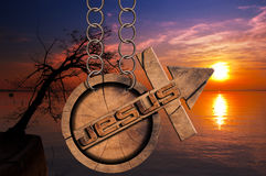 Jesus Wooden Symbol with Cross at the Sunset. Wooden symbol with cross and arrow upward and text Jesus. Hanging from a chain at a beautiful sunset over the lake Stock Image