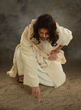 Jesus Writting in the Sand. Jesus using his finger to white in the sand stock images