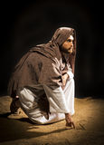 Jesuschrist praying. Jesus Christ writing in the sand in the dark black night Royalty Free Stock Images