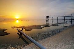 Jetée à la plage de Jeram pendant le coucher du soleil Photographie stock