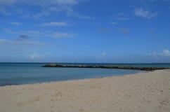 Jetée abandonnée de roche le long de la plage dans Aruba Image libre de droits