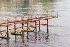 Jetée abandonnée rouillée en mer Photographie stock