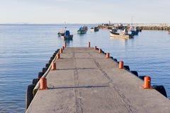 Jetée avec des bateaux de pêche ancrés dans la distance Photographie stock