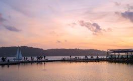 Jetée avec la silhouette de personnes et de voilier pendant le coucher du soleil Photo libre de droits