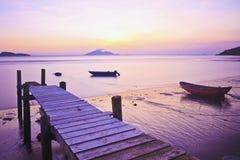 Jetée de coucher du soleil le long de la côte photographie stock libre de droits