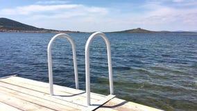 Jetée de terrasse avec une vue sur la mer et le coucher du soleil Échelle en acier de natation à une lumière du soleil banque de vidéos