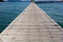 Jetée en bois dessus au-dessus de la belle plage avec le bleu Photographie stock