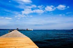 Jetée en bois dessus au-dessus de la belle plage avec le bleu Photo stock