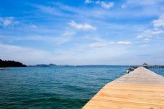 Jetée en bois dessus au-dessus de la belle plage avec le bleu Photos stock