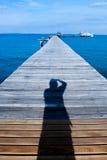 Jetée en bois dessus au-dessus de la belle plage avec le bleu Photographie stock libre de droits