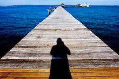 Jetée en bois dessus au-dessus de la belle plage avec le bleu Images stock