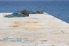 Jetée en pierre avec les filets de pêche colorés et la mer bleue Photos libres de droits
