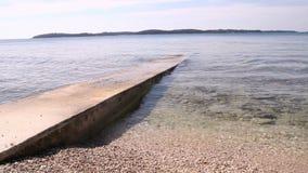 Jetée en pierre entourée avec la mer avec de petites vagues, petites pierres Vieille jetée en pierre pour la pêche et la Mer Adri banque de vidéos