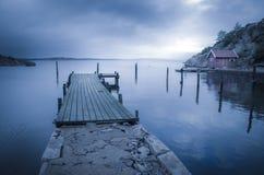 Jetée et hangar à bateaux par le fjord Images stock