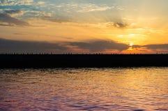 Jetée et mouettes dans le coucher du soleil Image stock