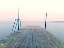 Jetée humide dans l'eau lisse de la baie de mer Taupe ancrée avec les poteaux en acier dans le fond images stock