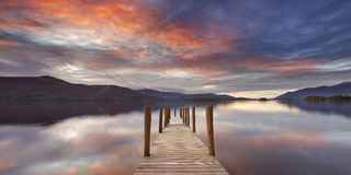 Jetée inondée dans le secteur de lac, Angleterre au coucher du soleil Image libre de droits