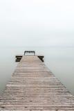Jetée par temps brumeux avec le banc à l'extrémité Photographie stock libre de droits