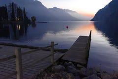 Jetée qui avance aux eaux calmes du lac pendant les heures égalisantes photographie stock