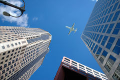 Jet Above Buildings. Corporate jet flying high above business district Royalty Free Stock Photography