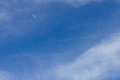 Jet across the sky with moon, of day Stock Image