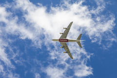 Jet aeroplane in flight. England. August 28 2014 : Underside view of a Boeing 777 jet aeroplane with Emirates  logo. Plane in flight with blue sky background Royalty Free Stock Photo