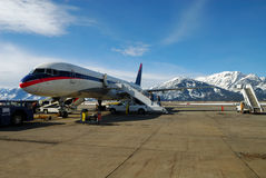 Jet Aircraft. People Boarding a Jet Airplane with snow covered mountains in background Royalty Free Stock Photo