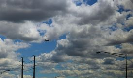 Jet aircraft in a blue cloudy sky is maneuvering for landing. Panoramic composition Royalty Free Stock Photo