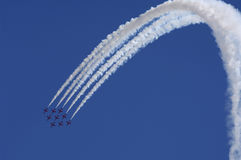 Jet aircraft in formation. The Red Arrows, the Royal Air Force Aerobatic Team flying fighter jets in close formation as they perform a sweeping loop against a Stock Photo