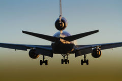 Jet aircraft landing at sunset Stock Photos