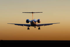 Jet aircraft landing at sunset Stock Image