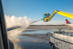 Jet aircraft wing being de-iced. Jet wing being de-iced. Detroit Metro Airport DTW, USA stock photo