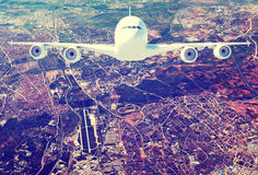 Jet airliner against aerial view of city Royalty Free Stock Image