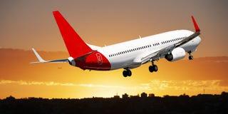 Jet Airliner Flying dans un ciel nuageux de stratus de couleur orange photographie stock libre de droits