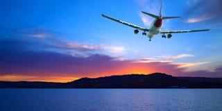 Jet Airliner Flying dans un cramoisi et un bleu a coloré le ciel de coucher du soleil photos libres de droits