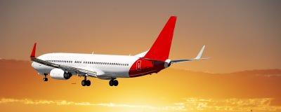Jet Airliner Flying in einem bewölkten Himmel des orangefarbenen Stratus stockbild