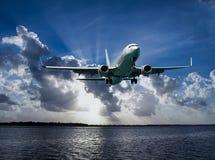Jet Airliner Flying en subeams et ciel nuageux de cumulonimbus images libres de droits