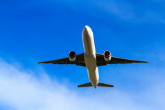 Jet airliner flying under blue sky Stock Photo
